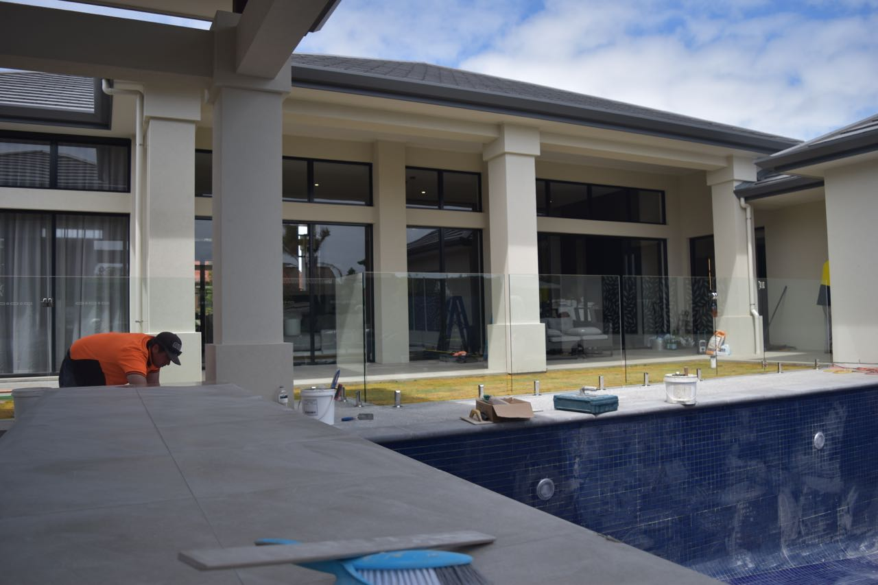 On site, installing a frameless fence for this pool in the Hospital Research Home Lottery lavish home built by Scott Salisbury Homes